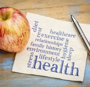 health concept - word cloud of contributing factors (diet, lifestyle, healthcare, family history, environment, exercise, stress, relationships, sleep, rest, hygiene) on a napkin with an apple